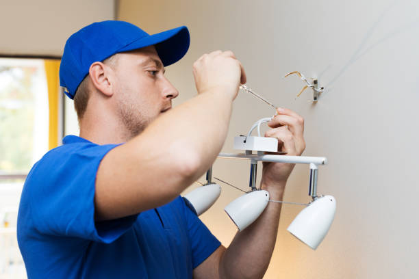 electrician at work — installing lamp on the wall